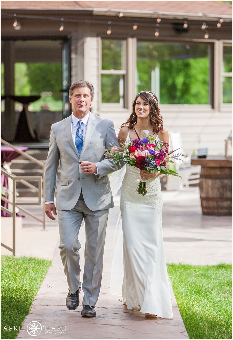 Bride-walks-down-the-aisle-with-her-dad-at-Wedgewood-on-Boulder-Creek-in-Colorado.jpg